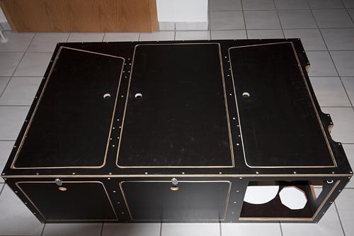 Die Box von hinten aus gesehen. In der rechten Kammer sind Aussparungen für Wassertank, Kocher, Gaslampe und Espressokocher. Dadurch verrutschen diese Gegenstände nicht. Die Aussparungen am rechten Rand der Box sind dazu da, dass man noch an die Seitenfächer des Tepee kommt.