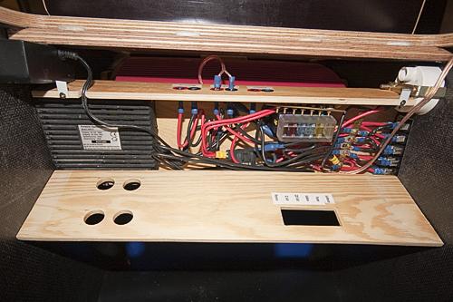 Links oben der 12 Volt Verteiler, darunter der 220 Volt Wechselrichter, in der Mitte die Anschlüsse für Kühlbox und Pumpe (+ 1x Reserve), der Sicherungskasten und die Klemmen der Schalter. Darüber ist das Voltmeter.
